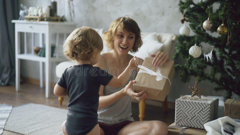 La madre feliz y su pequeña hija desempaquetan la caja de regalo cerca del árbol de navidad en casa foto de archivo