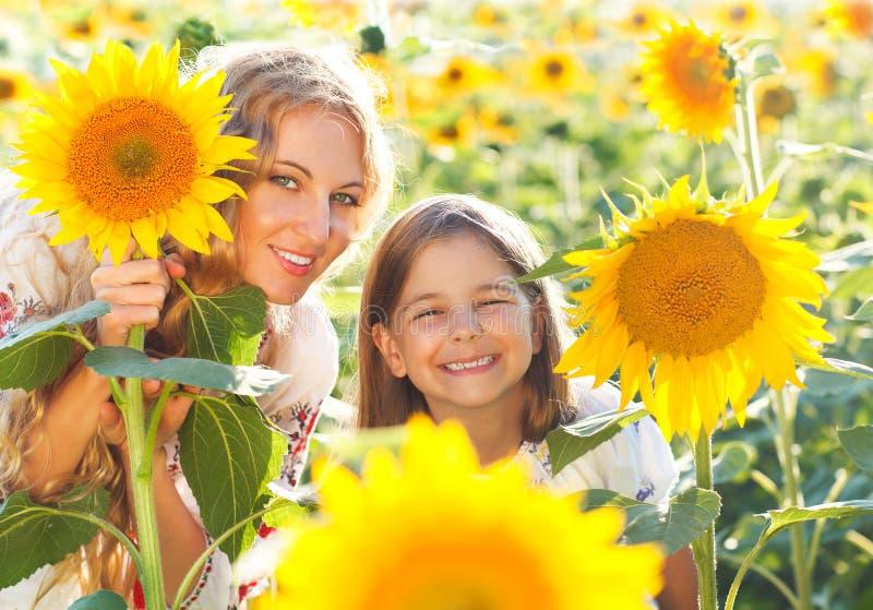 La madre feliz y su pequeña hija en el girasol colocan imágenes de archivo libres de regalías