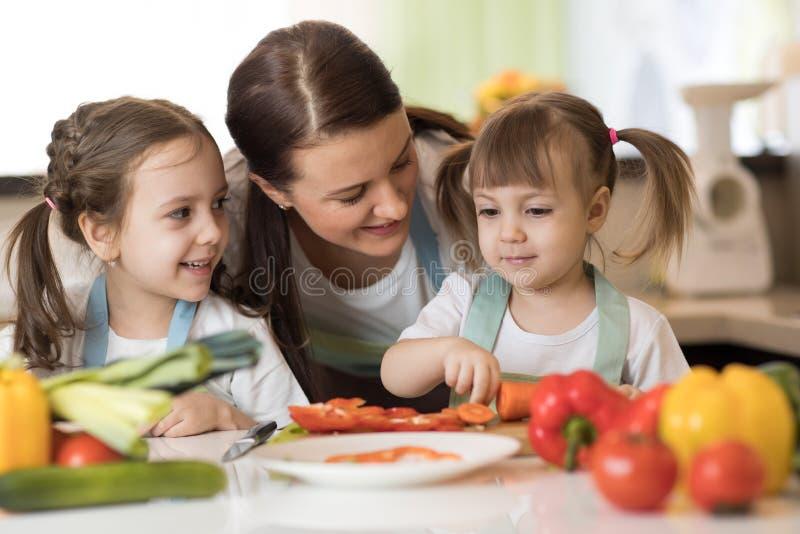 La madre feliz y sus hijas gozan el hacer de la comida sana juntas foto de archivo