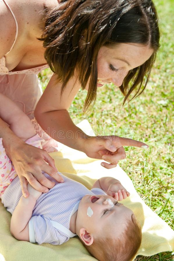 La madre fornisce la protezione del sole al bambino immagine stock