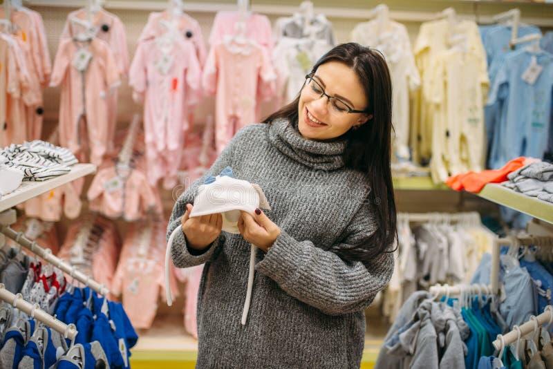 La madre futura sorridente sceglie il cappello del bambino fotografia stock