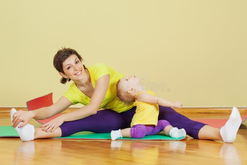 La madre hace ejercicios con su hija foto de archivo