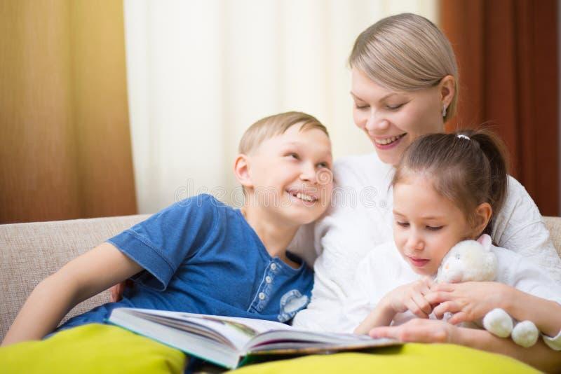La madre hermosa está leyendo un libro a sus niños jovenes La hermana y el hermano está escuchando una historia imágenes de archivo libres de regalías