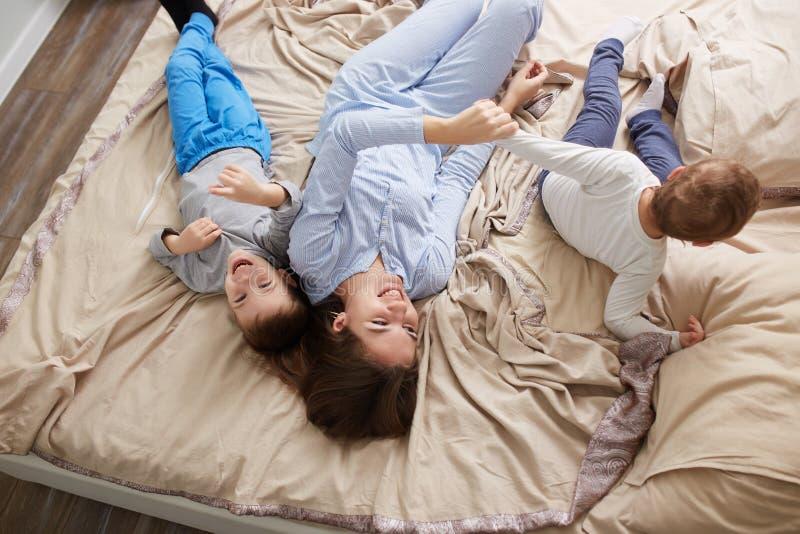 La madre hermosa feliz vestida en pijama azul claro pone con sus dos pocos hijos en la cama con la manta beige en fotografía de archivo