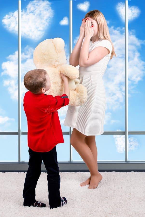 La madre hermosa joven se cerró los ojos con sus manos, hijo da a mamá un regalo, una sorpresa, un oso de peluche blanco grande C fotografía de archivo