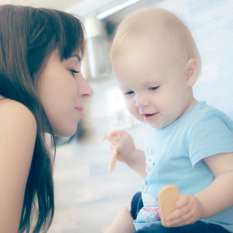 La madre hermosa que juega con su niño hermoso, el niño come la galleta y las risas fotografía de archivo