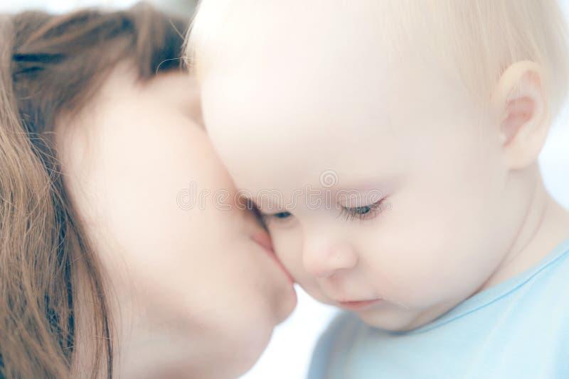 La madre hermosa que juega con su niño hermoso, el niño come la galleta y las risas imagen de archivo