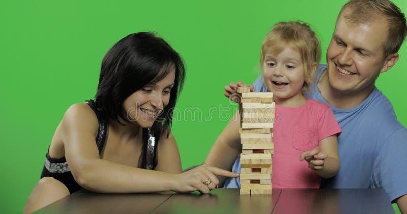 La madre, il padre e la figlia gioca il jenga Tira i blocchi di legno dalla torre fotografia stock libera da diritti