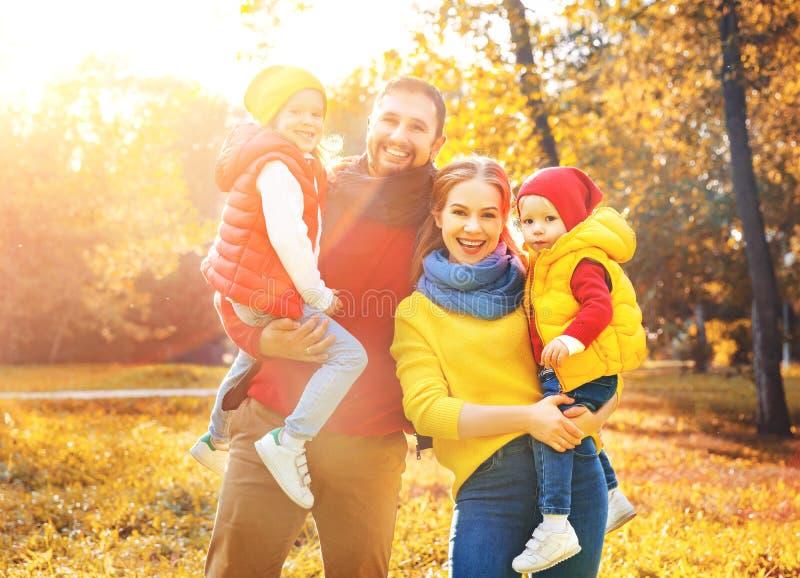 La madre, il padre ed i bambini felici della famiglia su un autunno camminano fotografia stock libera da diritti