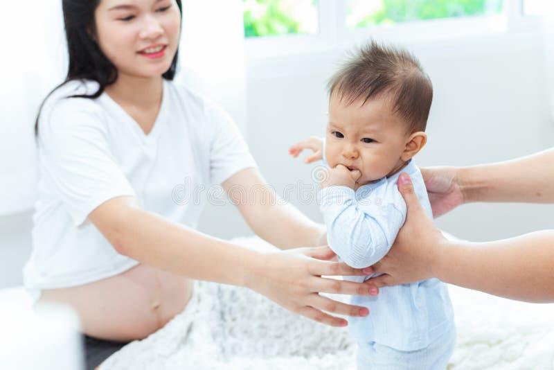 La madre incinta sta prendendo suo figlio si alza ma il ragazzo lo ha espresso non è stato soddisfatto immagini stock