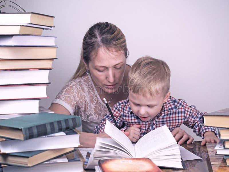 La madre insegna al figlio a leggere fra le pile di libri immagini stock libere da diritti