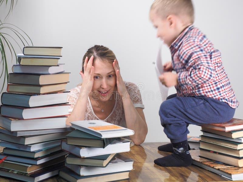 La madre insegna al figlio a leggere fra le pile di libri fotografie stock