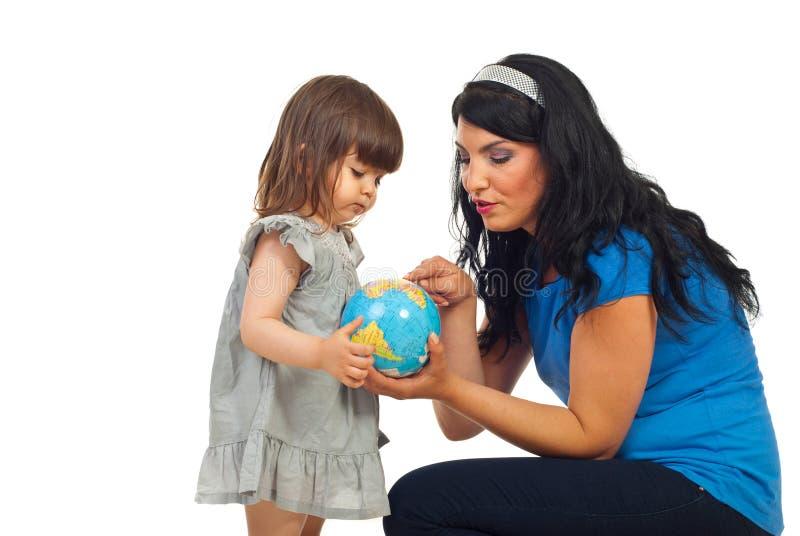 La madre insegna alla figlia circa il globo del mondo immagini stock