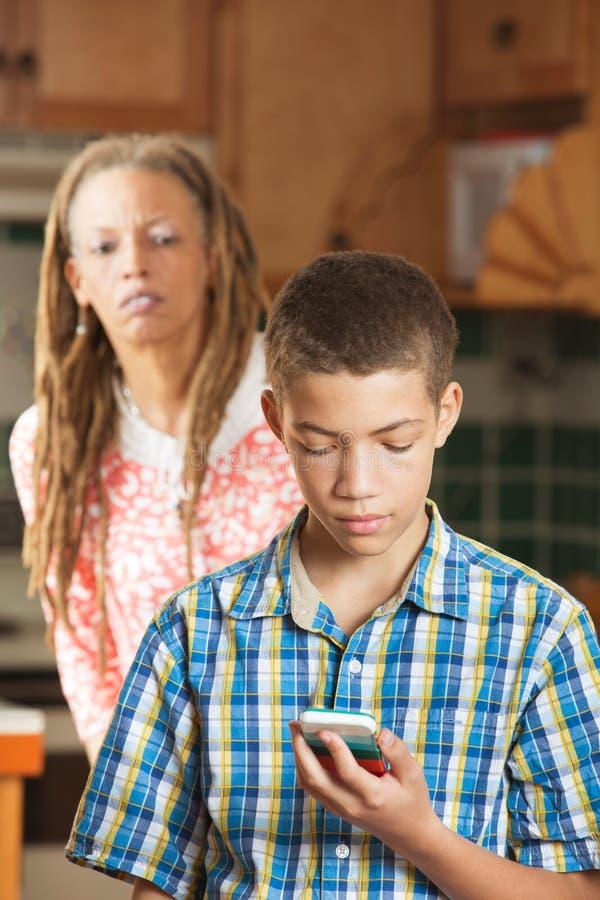 La madre intenta mirar a escondidas mientras que el hijo adolescente comprueba su teléfono móvil fotos de archivo