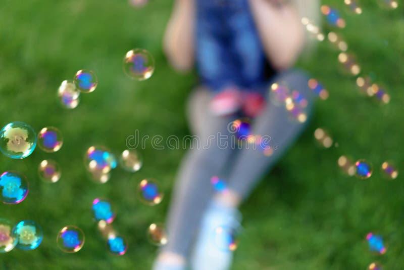 La madre irreconocible Unfocused infla burbujas de jabón con su pequeño hijo en un parque en un día de verano soleado foco en las fotografía de archivo