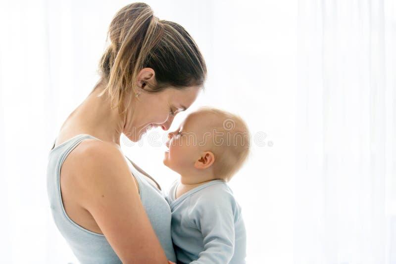 La madre joven, abrazando con dulzura y cuida a su bebé, s imágenes de archivo libres de regalías