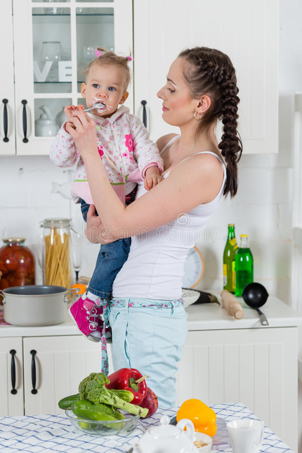 La madre joven alimenta al niño en la cocina. fotografía de archivo