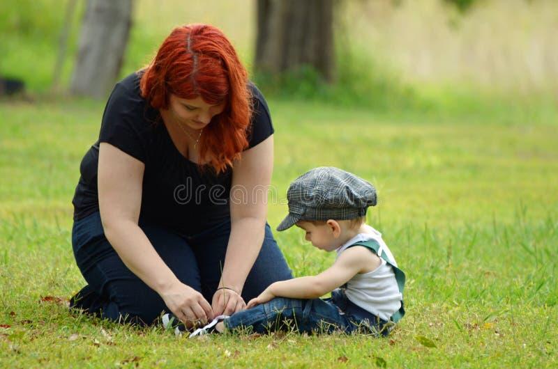 La madre joven cariñosa implica cordones de zapato del hijo de los niños pequeños imágenes de archivo libres de regalías