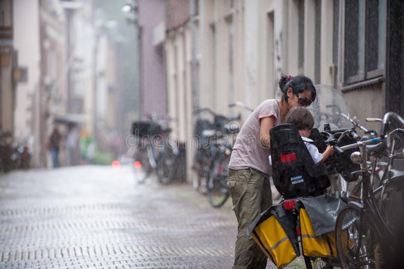 La madre joven coloca a su niño en la bici en la lluvia Amsterdam imagen de archivo libre de regalías
