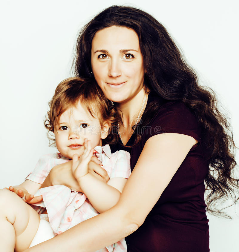La madre joven con la pequeña hija linda en blanco, interior sonriente feliz de la familia aisló adorable, gente moderna de la fo foto de archivo libre de regalías