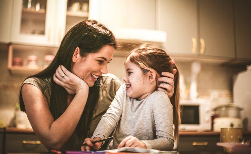 La madre joven con su niña se ríe junto imagen de archivo libre de regalías