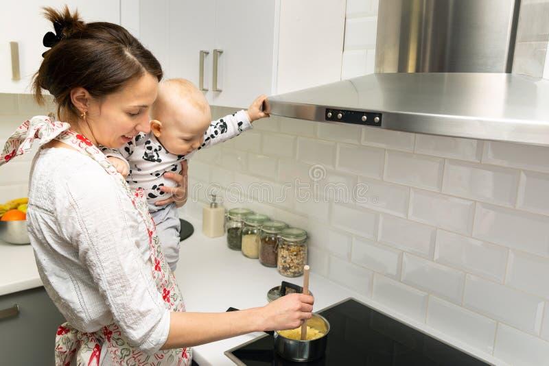 La madre joven con un bebé en sus manos cocina la comida en un pote en la estufa foto de archivo