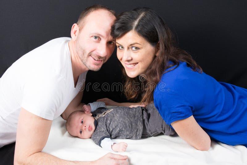 La madre joven del padre y el bebé lindo que mienten en piso abrazan y besan al padre foto de archivo