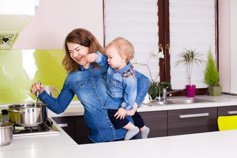 La madre joven enseña al pequeño bebé a cocinar imagenes de archivo