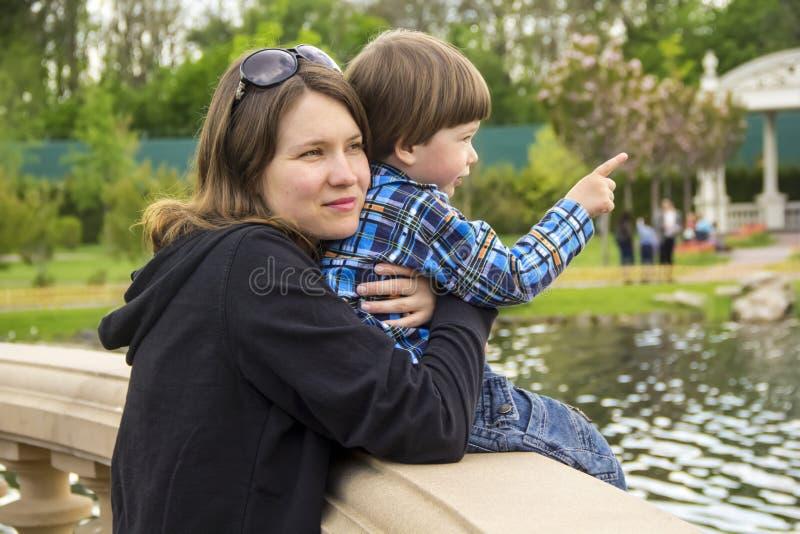 La madre joven es de abrazo y que detiene a su pequeño hijo que se sienta en el puente cerca del lago y que señala en algo con su fotografía de archivo libre de regalías
