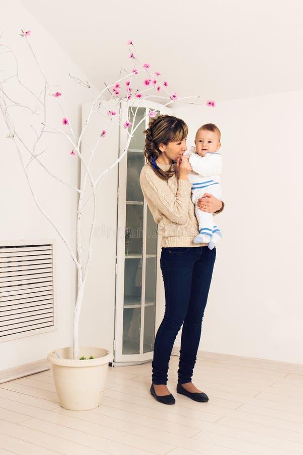 La madre joven está celebrando al pequeño bebé dentro fotografía de archivo libre de regalías