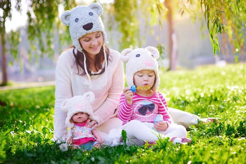 La madre joven feliz y su la hija que juegan en verano parquean imagenes de archivo