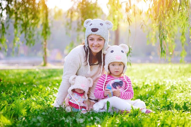 La madre joven feliz y su la hija que juegan en verano parquean imagen de archivo