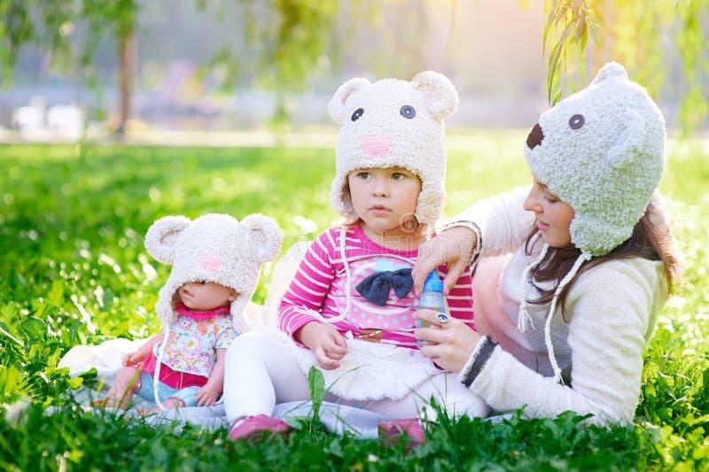 La madre joven feliz y su la hija que juegan en verano parquean fotos de archivo