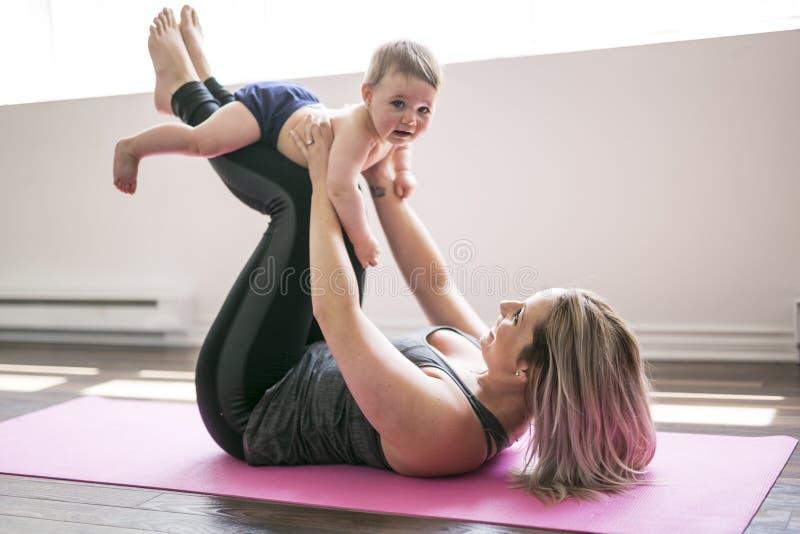 La madre joven hace ejercicios físicos de la yoga así como su bebé fotografía de archivo libre de regalías