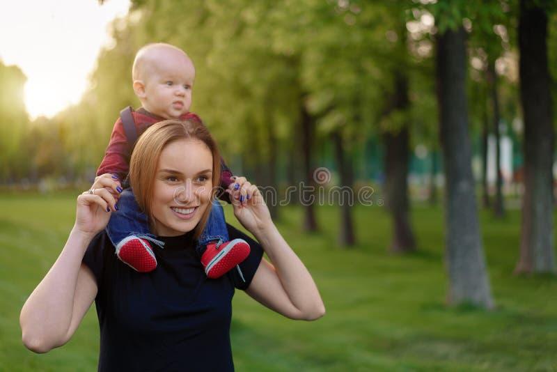 La madre joven hermosa camina con su pequeño hijo en un parque del verano fotos de archivo