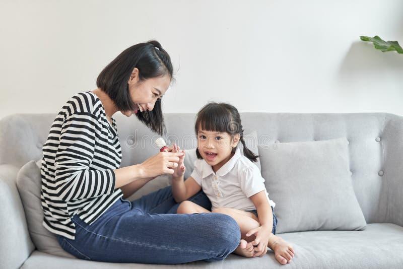 La madre joven hermosa est? pintando el barniz de clavo a su peque?a hija linda fotografía de archivo libre de regalías