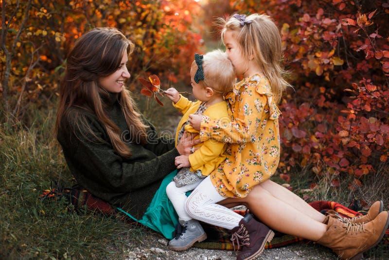La madre joven hermosa y su pequeña la hija que caminan en verano parquean Mujer y muchacha linda del niño que pasan el tiempo ju fotografía de archivo