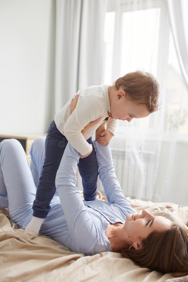 La madre joven vestida en pijama azul claro pone en la cama con la manta beige y detener a su pequeño hijo en sus manos en fotos de archivo