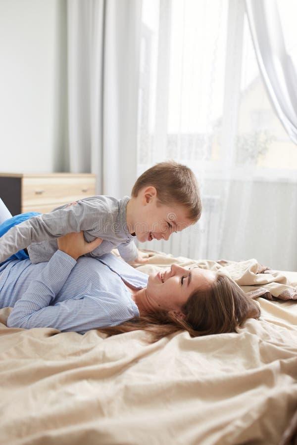 La madre joven vestida en pijama azul claro pone en la cama con la manta beige y detener a su peque?o hijo en sus manos en imagenes de archivo