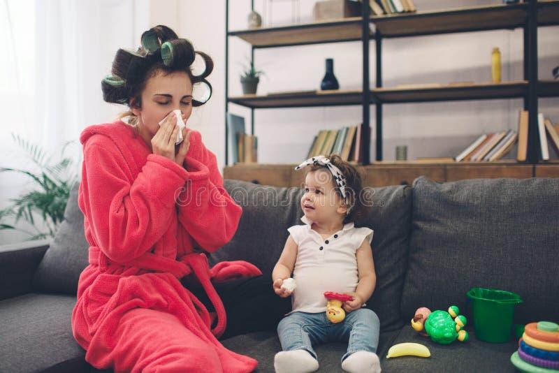 La madre joven vieja está experimentando la depresión postnatal Mujer triste y cansada con PPD Ella no quiere jugar con ella imagenes de archivo