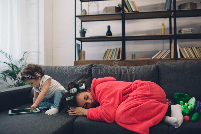 La madre joven vieja está experimentando la depresión postnatal Mujer triste y cansada con PPD Ella no quiere jugar con ella imagen de archivo