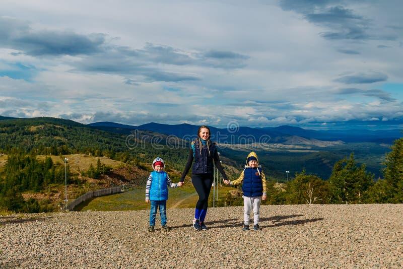 La madre joven y dos niños caen en las montañas imagenes de archivo