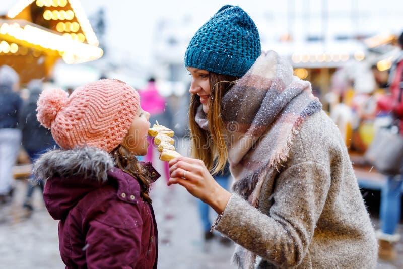 La madre joven y la hija que comían el chocolate blanco cubrieron las frutas en el pincho en mercado alemán tradicional de la Nav foto de archivo libre de regalías