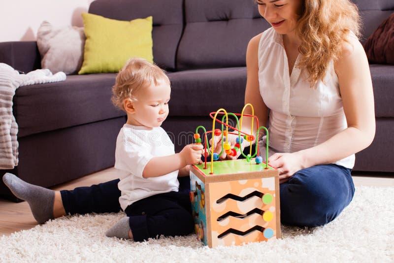 La madre joven y su bebé juegan el juguete de madera en el piso foto de archivo libre de regalías