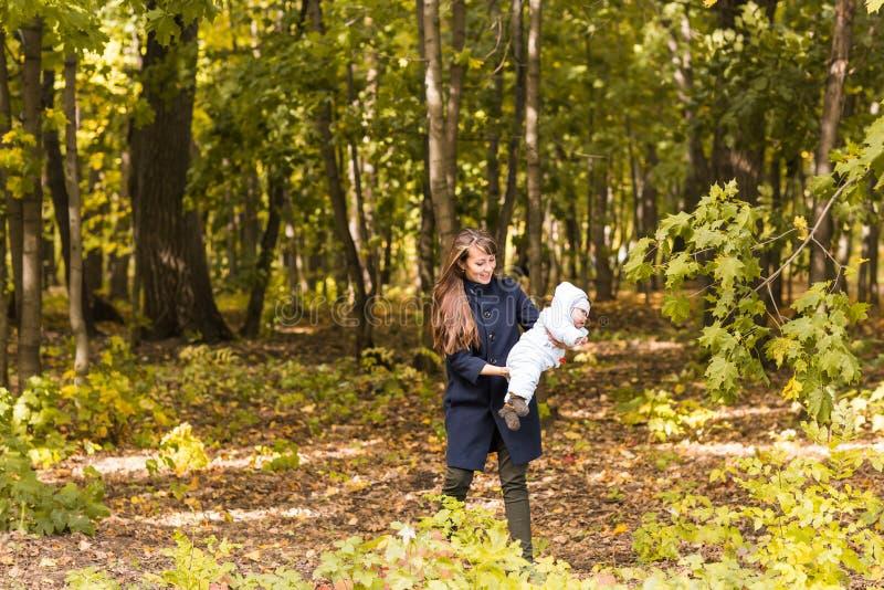 La madre joven y su niña pequeña se divierten en otoño fotos de archivo