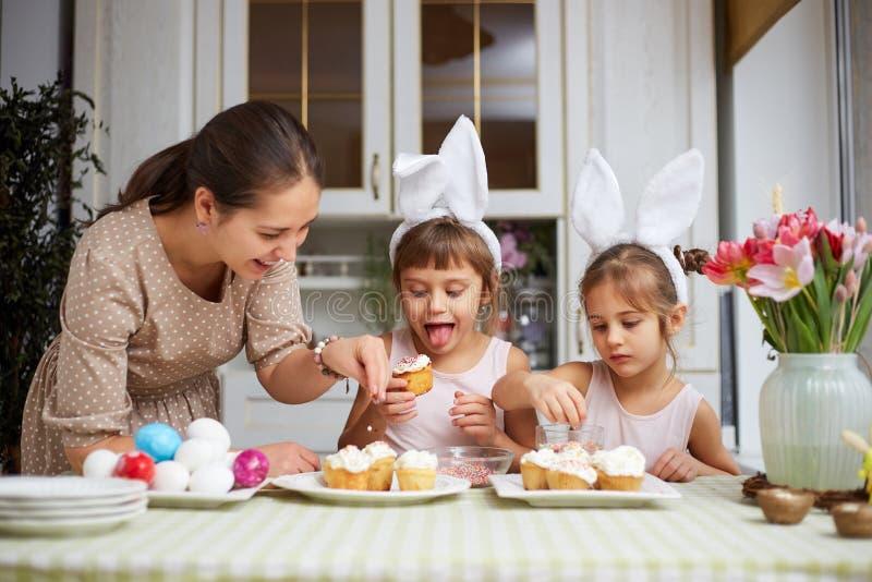 La madre joven y sus dos pequeñas hijas con los oídos de conejo blancos en sus cabezas cocinan las pequeñas tortas de Pascua para foto de archivo