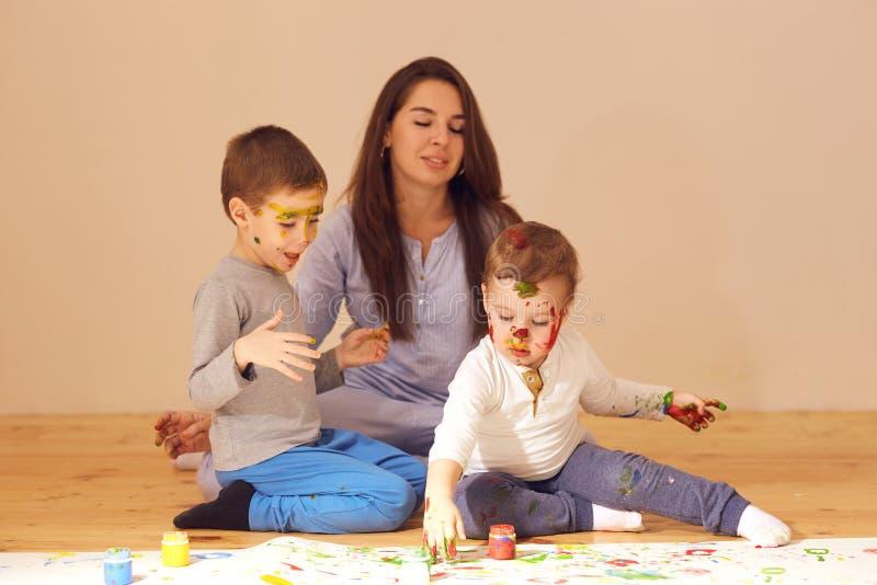 La madre joven y sus dos peque?os hijos con las pinturas en sus caras vestidas en la ropa casera se est?n sentando en el de mader imagen de archivo