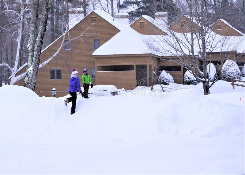 La madre juega con el hijo en snowbank imagen de archivo