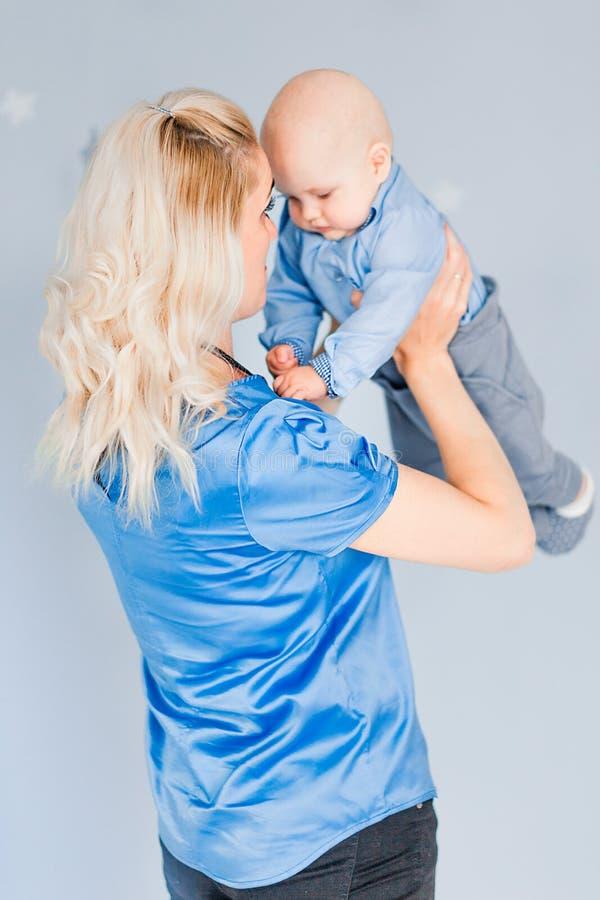 La madre juega y lanza para arriba a un niño en el cuarto de niños contra la perspectiva de la pared azul fotos de archivo