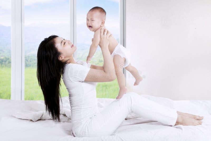 La madre lanza para arriba a su bebé imágenes de archivo libres de regalías